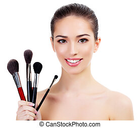 Pretty woman with makeup brushes, isolated on white