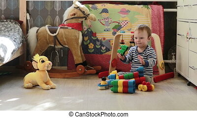 Little cute boy playing with toys in the room