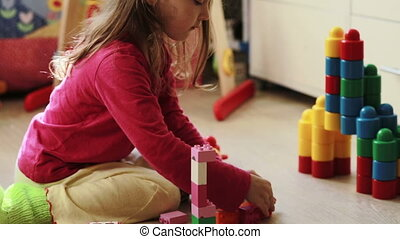 Cute little girl playing with toy blocks at home in the...
