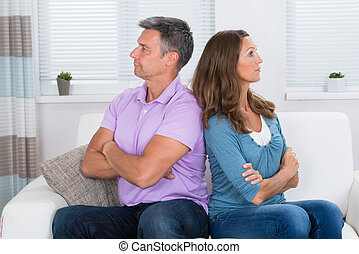 Unhappy Couple Sitting On Sofa - Unhappy Mature Couple With...