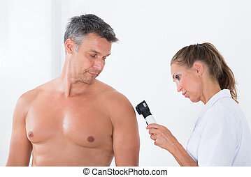 Doctor Examining Pigmented Skin Of Patient - Female Doctor...