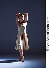 Young beautiful dancer in beige dress dancing on gray...