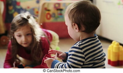 baby boy playing with his sister in the nursery - baby boy...