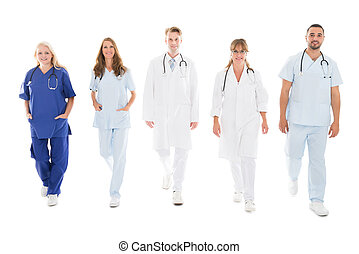 Portrait Of Confident Medical Team Walking In Row - Full...