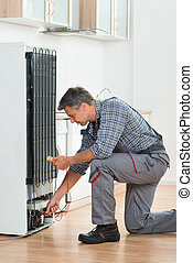 Technician Checking Fridge With Multimeter At Home - Full...