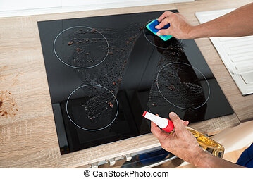 Janitor Cleaning Induction Stove In Kitchen - Cropped image...