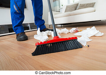 Janitor Sweeping Crumpled Papers On Floor - Low section of...