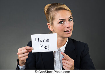 Businesswoman Holding Paper With Hire Me Text - Portrait of...