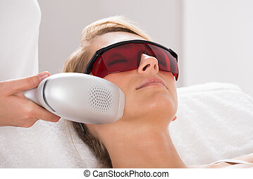 Woman Undergoing Laser Treatment At Salon - Closeup of young...