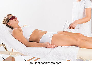 Woman Receiving Laser Treatment On Leg - Young woman...