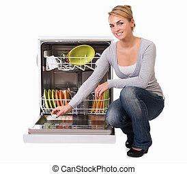 Young Woman Placing Soap In Dishwasher - Full length of...