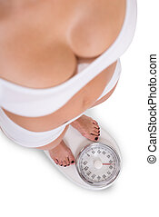 Woman Checking Weight Over White Background - Low section of...