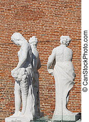 ancient statues with the background red brick wall - old...