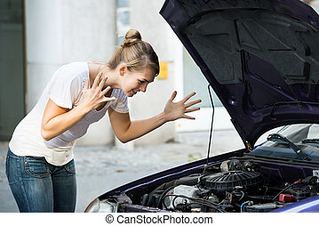 Frustrated Woman Looking At Broken Down Car Engine -...