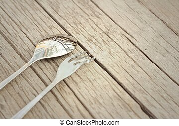 Spoon and fork on a background of brown wood