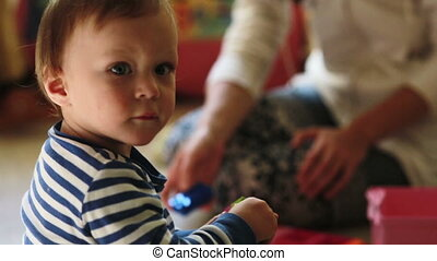 mother playing with her baby boy with toys