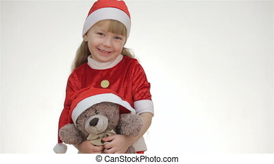 Kid girl hugging a teddy bear. - Kid girl in a red suit and...