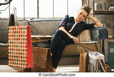 Tired brunet woman sitting on couch among shopping bags in...