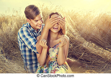 Happy couple having fun outdoors on wheat field, love concept
