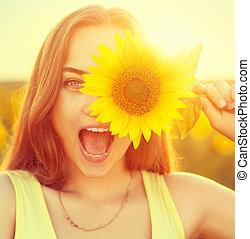 Beauty joyful teenage girl with sunflower