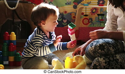 mother playing with her baby boy with toys - mother playing...