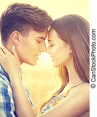 Happy couple kissing and hugging outdoors on wheat field,...