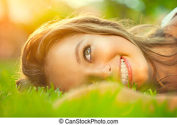 Beauty teenage romantic girl lying on the grass close-up