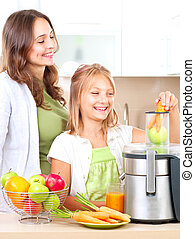 Happy family making fresh apple and carrot juice
