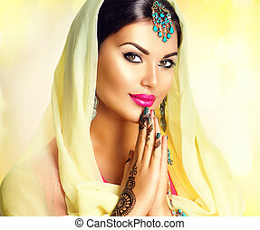 Beauty Indian girl with mehndi tattoos hold palms together