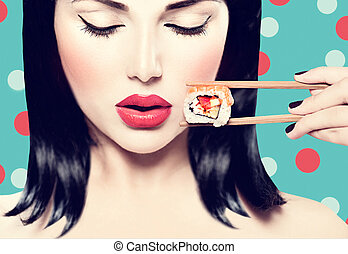 Beautiful woman holding chopsticks with sushi roll