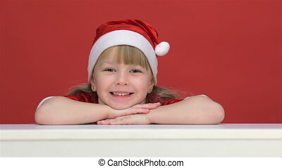 Kid resting his chin on his hands - Kid girl in a red suit...