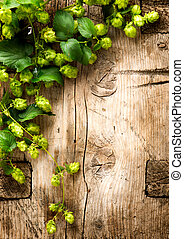 Hop twig over wooden cracked table background. Vintage toned