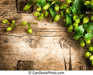 Hop twig over old wooden table background. Vintage style....