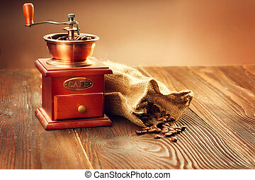 Coffee mill with burlap sack full of roasted coffee beans...