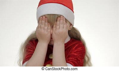 Kid girl laughs - Kid girl in a red suit and Santa hat...