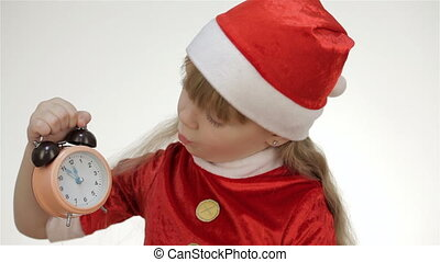Kid girl looking at the clock and wondering - Kid girl in a...