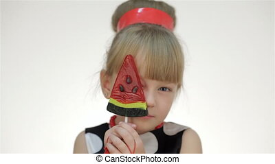Girl covers her eyes lollipop. Kid girl posing in studio...