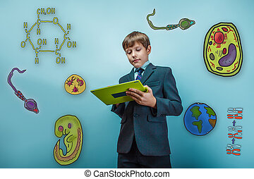 Boy in a business suit student working on the tablet keen...
