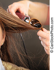 Stylist curling hair for young woman. - Stylist curling hair...