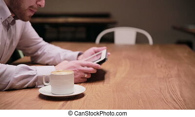 Young businessman working on tablet in cafe - Young...