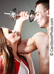 Couple muscular man and girl admiring his strength -...