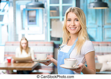 Pleasant waitress holding cup - Hard working waitress. Close...