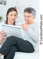 Reading a newspaper with an old lady