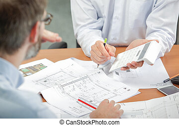 Two men discussing blueprints, holding calculator