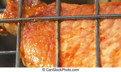 Grilled juicy pork steaks over coals, on the brazier, macro