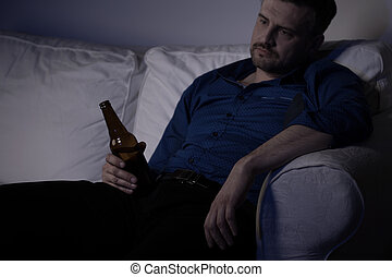 Heartbroken man feeling miserable and drinking alone