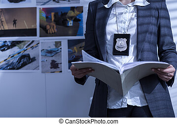 Reviewing files and documents - Police woman is reviewing...