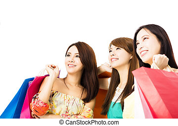 Group of happy young woman with shopping bags looking up