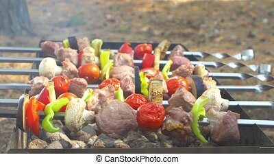 Assorted meat from chicken, pork and various vegetables for barbecue on grill, turning around