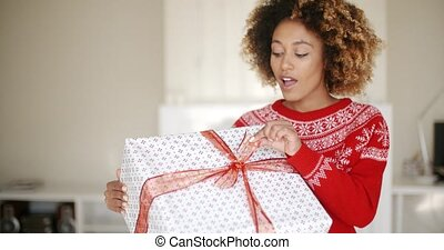 Pretty Young Woman Opening Christmas Gift - Pretty Young...